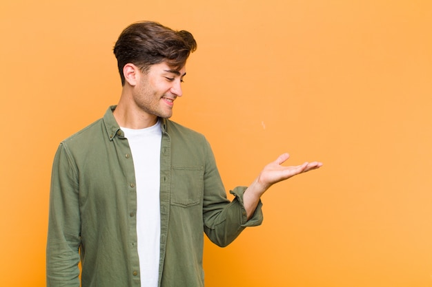 Young handsome man feeling happy and smiling casually, looking to an object or concept held on the hand on the side against orange wall