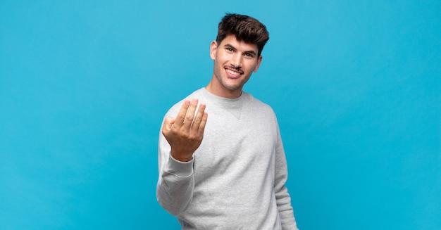 Молодой красивый мужчина чувствует себя счастливым, успешным и уверенным в себе, сталкивается с проблемой и говорит: давай! или приветствуя вас