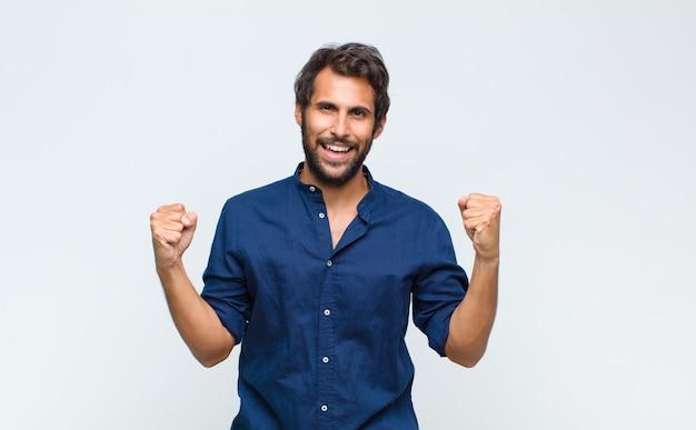 Молодой красивый мужчина чувствует себя счастливым, удивленным и гордым, кричит и празднует успех с широкой улыбкой