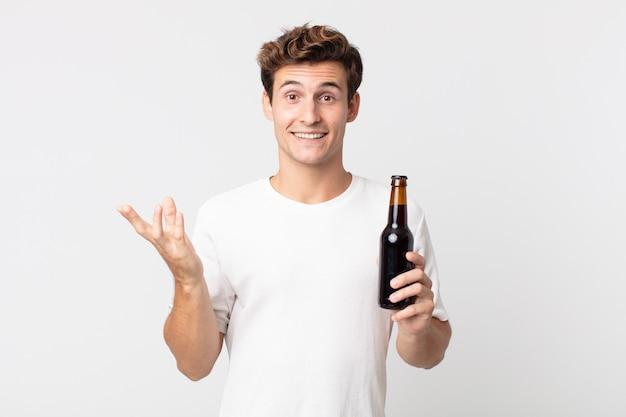 幸せを感じ、解決策やアイデアを実現し、ビール瓶を持って驚いた若いハンサムな男