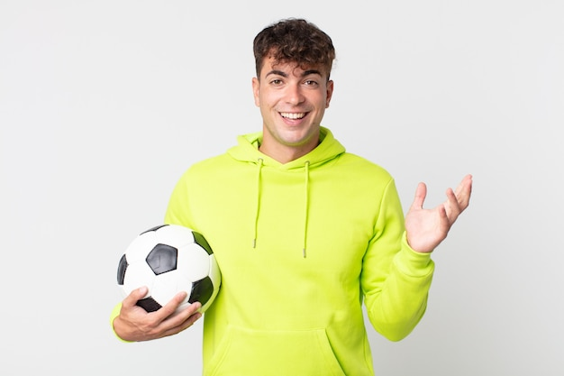 Young handsome man feeling happy, surprised realizing a solution or idea and holding a soccer ball