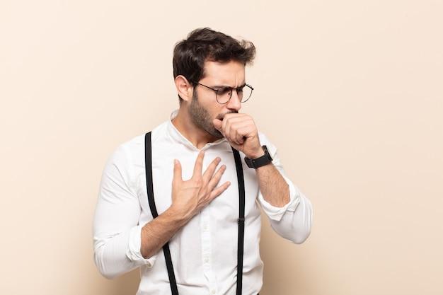 喉の痛みとインフルエンザの症状で気分が悪くなり、口を覆って咳をする若いハンサムな男