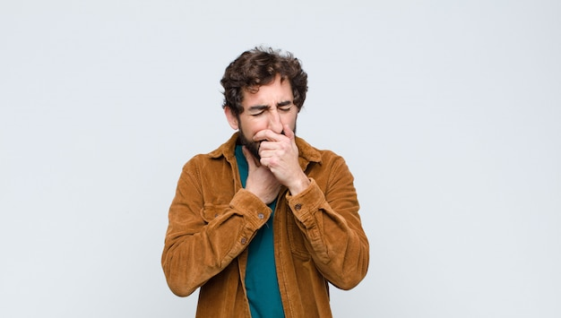 Young handsome man feeling ill with a sore throat and flu symptoms, coughing with mouth covered against wall