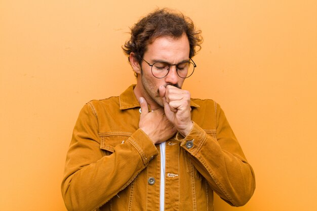 Young handsome man feeling ill with a sore throat and flu symptoms, coughing with mouth covered over orange wall