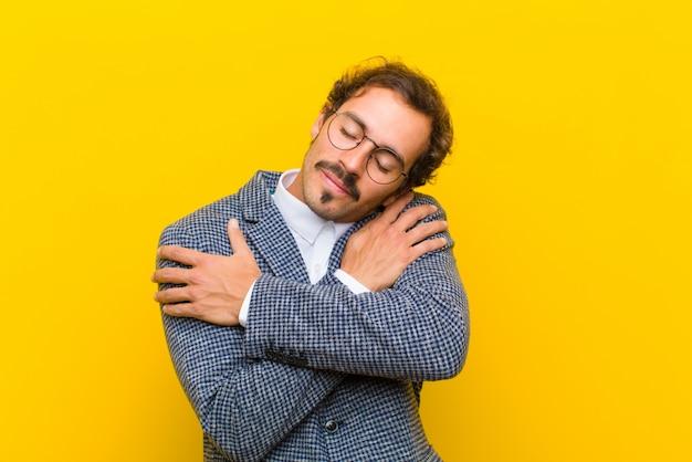 若いハンサムな男の愛、笑顔、抱きしめると抱きしめて、独身、利己的でエゴセントリックなオレンジ色の壁