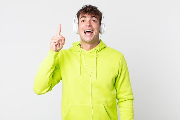 アイデアとヘッドフォンを実現した後、幸せで興奮した天才のように感じる若いハンサムな男