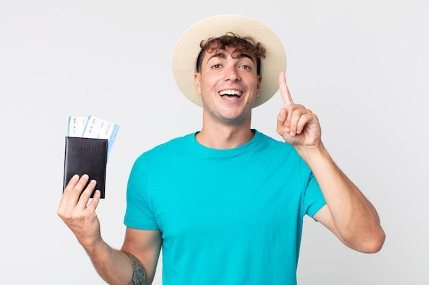 아이디어를 실현 한 후 행복하고 흥분된 천재처럼 느끼는 젊은 잘 생긴 남자. 여권을 들고 있는 여행자