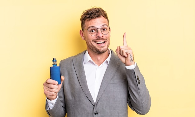 Young handsome man feeling like a happy and excited genius after realizing an idea. vaporizer concept