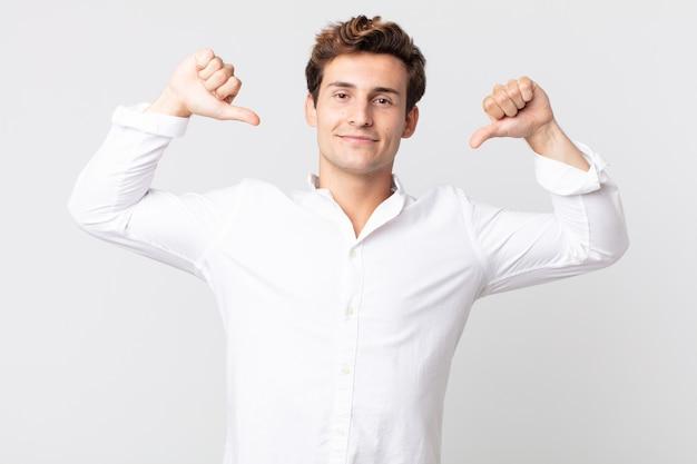 Молодой красивый мужчина чувствует себя гордым, высокомерным и уверенным, выглядит довольным и успешным, указывая на себя
