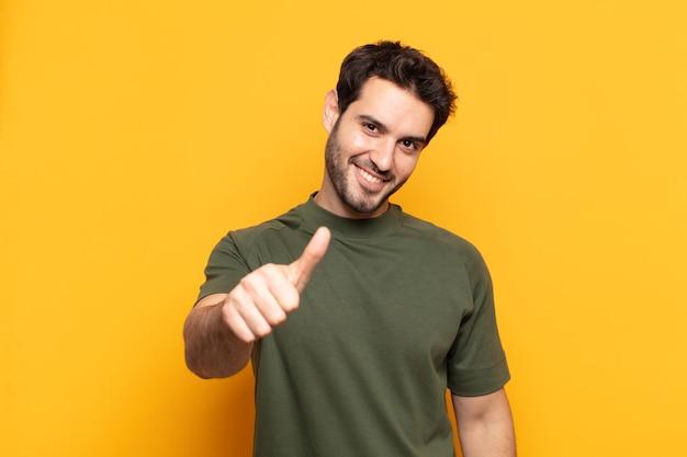 誇り、のんき、自信を持って幸せを感じ、親指を立てて前向きに笑っている若いハンサムな男