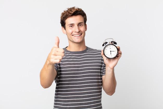 誇らしげに感じ、親指を立てて前向きに笑って、目覚まし時計を持っている若いハンサムな男