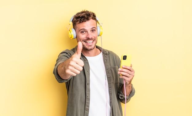 젊고 잘생긴 남자는 자랑스러워하고, 헤드폰과 스마트폰 개념을 엄지손가락으로 들고 긍정적으로 웃고 있습니다.