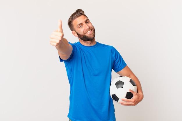親指を立てて前向きに笑って、誇りを感じている若いハンサムな男。サッカーのコンセプト
