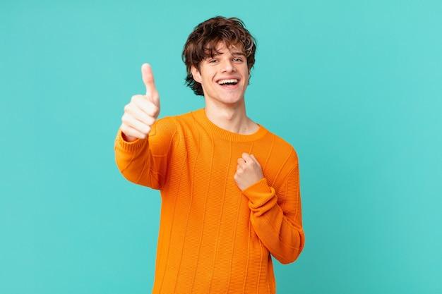 誇らしげに感じ、親指を立てて前向きに笑っている若いハンサムな男