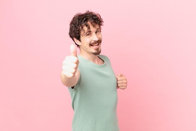 Молодой красавец чувствует гордость, позитивно улыбается, показывает палец вверх