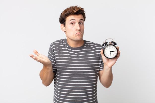 困惑して混乱し、目覚まし時計を疑って保持していると感じている若いハンサムな男