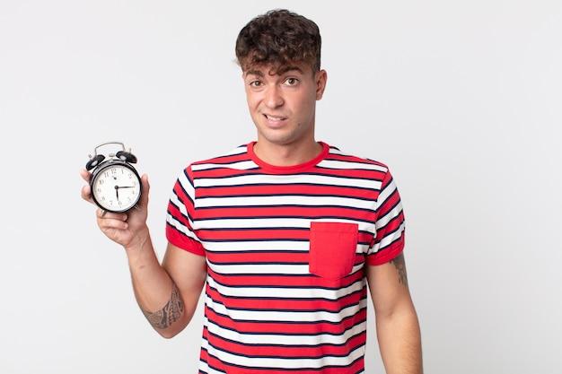 困惑して混乱し、目覚まし時計を持っている若いハンサムな男