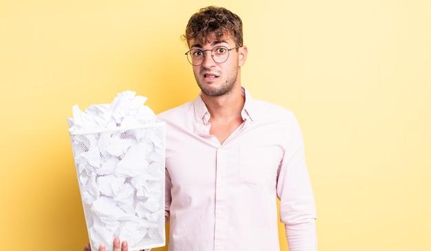 困惑と混乱を感じている若いハンサムな男。紙球ゴミ箱の概念