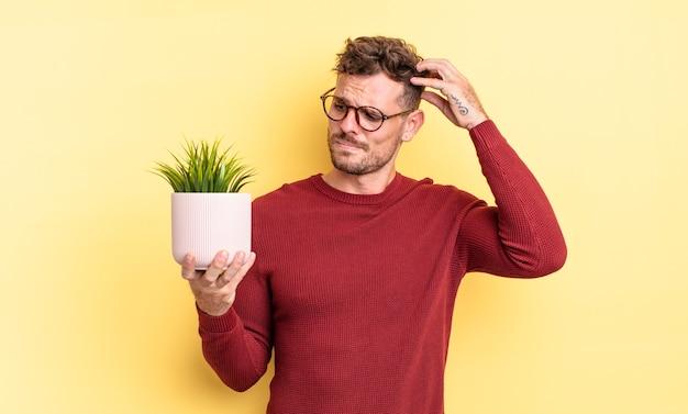 Молодой красивый мужчина чувствует себя озадаченным и сбитым с толку, почесывая голову. концепция декоративного растения
