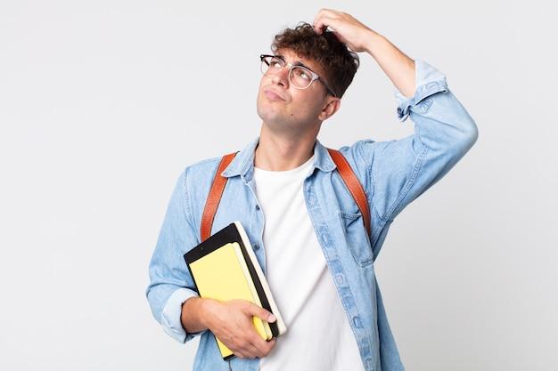 Молодой красавец чувствует себя озадаченным и сбитым с толку, почесывая голову. концепция студента университета