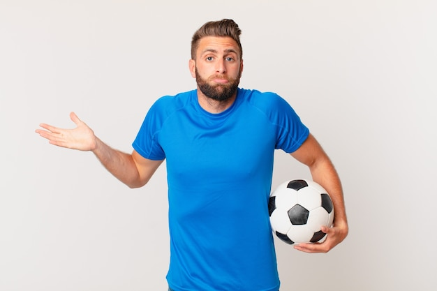 Young handsome man feeling puzzled and confused and doubting. soccer concept