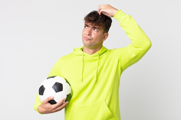 Young handsome man feeling puzzled and confused, scratching head and holding a soccer ball