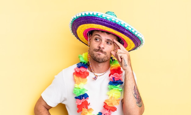 Young handsome man feeling puzzled and confused, scratching head. mexican party concept