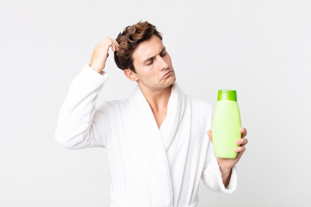 Young handsome man feeling puzzled and confused, scratching head with bathrobe and holding a shampoo bottle
