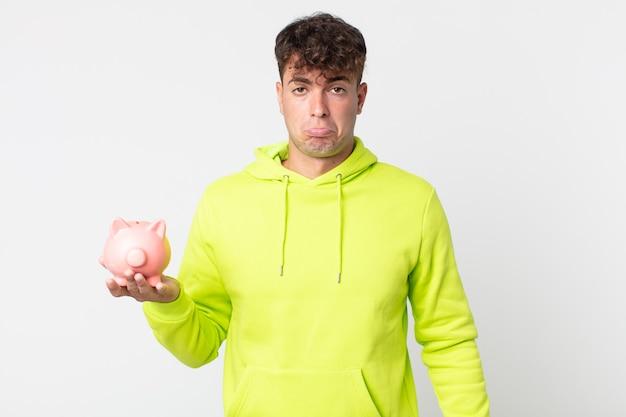 不幸な表情で悲しみと泣き言を感じ、泣いて貯金箱を持っている若いハンサムな男