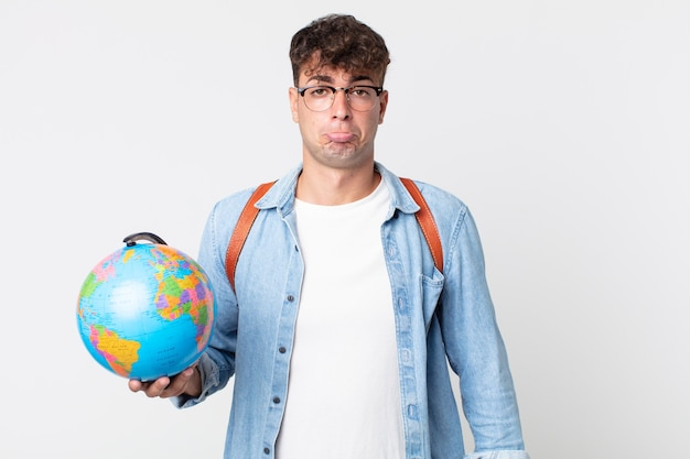 不幸な表情と泣き悲しみと泣き言を感じている若いハンサムな男。世界の地球地図を持っている学生