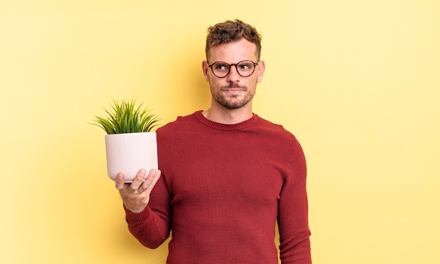 Young handsome man feeling sad, upset or angry and looking to the side. decorative plant concept