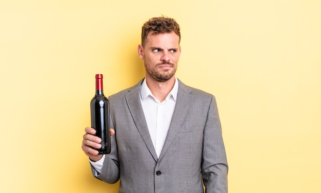 젊고 잘생긴 남자는 슬프거나 화가 나거나 화가 나서 옆을 바라보고 있습니다. 와인 개념의 병