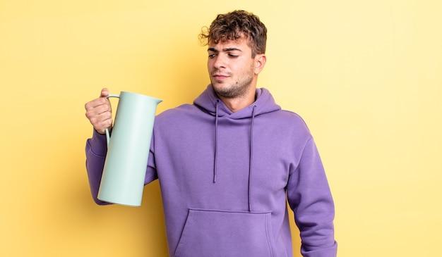 若いハンサムな男は、悲しみ、動揺、または怒りを感じ、横を向いています。魔法瓶のコンセプト