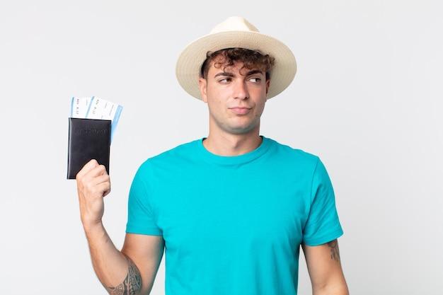 젊고 잘생긴 남자는 슬프거나 화가 나거나 화가 나서 옆을 바라보고 있습니다. 여권을 들고 있는 여행자