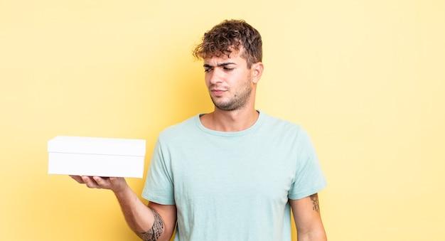 若いハンサムな男は、悲しみ、動揺、または怒りを感じ、横を向いています。ホワイトボックスのコンセプト
