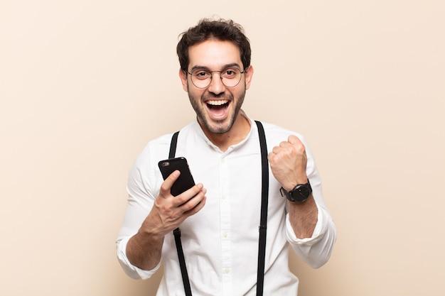 Молодой красивый мужчина потрясен, взволнован и счастлив, смеется и празднует успех, говоря