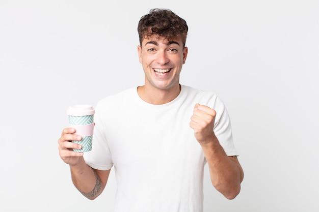 젊고 잘생긴 남자는 충격을 받고 웃고 성공을 축하하고 테이크 아웃 커피를 들고 있다
