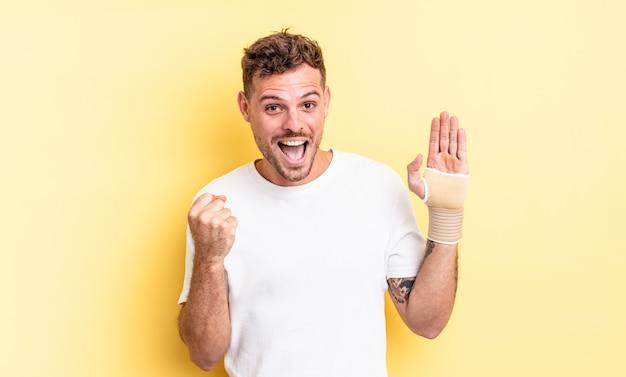 若いハンサムな男はショックを受け、笑い、成功を祝っています。手の包帯の概念
