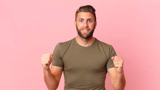 Молодой красивый мужчина в шоке, смеется и празднует успех