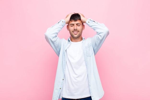 Молодой красавец, чувствуя стресс и беспокойство, подавленный и разочарованный головной болью, поднимает обе руки к голове о розовую стену