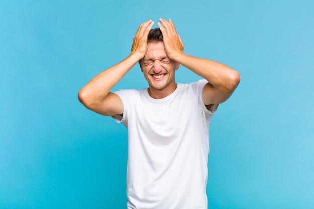 스트레스와 불안, 우울, 두통으로 좌절감을 느끼는 젊은 잘 생긴 남자, 양손을 머리에 올리기