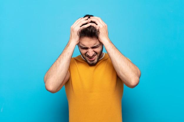 ストレスと欲求不満を感じ、手を頭に上げ、疲れ、不幸、片頭痛を感じている若いハンサムな男