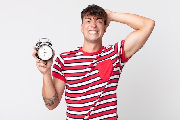 頭に手を置いて目覚まし時計を持って、ストレス、不安、または恐怖を感じている若いハンサムな男