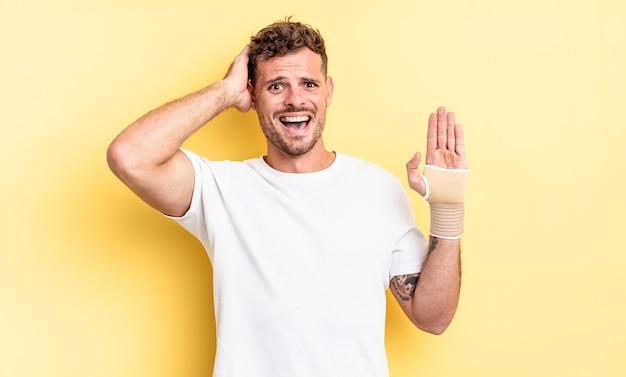 若いハンサムな男は、頭に手を置いて、ストレス、不安、または恐怖を感じています。手の包帯の概念
