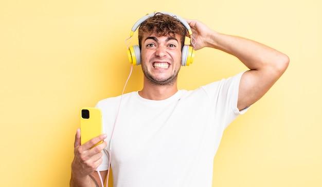 若いハンサムな男は、頭に手を置いて、ストレス、不安、または恐怖を感じています。ヘッドフォンとスマートフォンのコンセプト