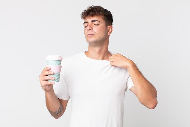 Молодой красивый мужчина чувствует стресс, беспокойство, усталость и разочарование и держит кофе на вынос