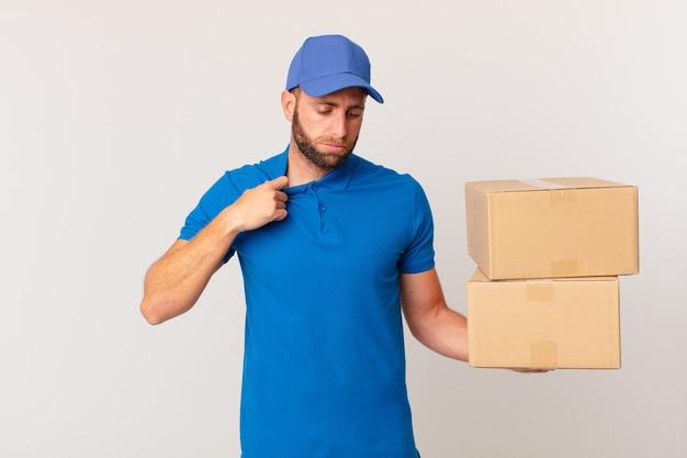 Молодой красивый мужчина чувствует себя напряженным, встревоженным, усталым и разочарованным. концепция доставки пакетов