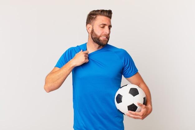 Молодой красивый мужчина чувствует себя напряженным, встревоженным, усталым и разочарованным. футбольная концепция