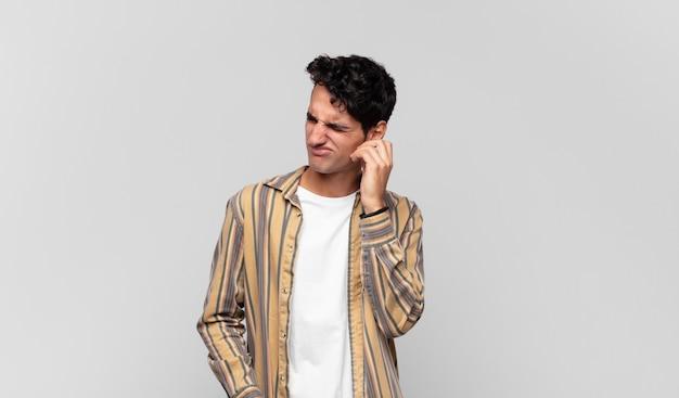 若いハンサムな男は、ストレス、欲求不満、疲れを感じ、痛みを伴う首をこすり、心配し、問題を抱えた表情で