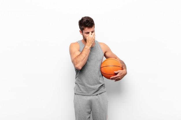 若いハンサムな男は、ストレスを感じ、不満と欲求不満を感じ、額に触れ、バスケットボールのボールを保持している激しい頭痛の片頭痛に苦しんでいます。